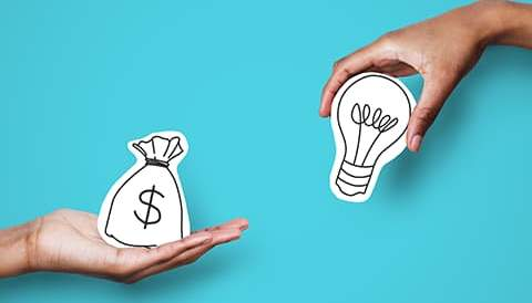 Two hands, one holding light bulb and other holding money icon